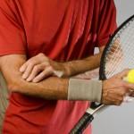 tennis player massaging elbow